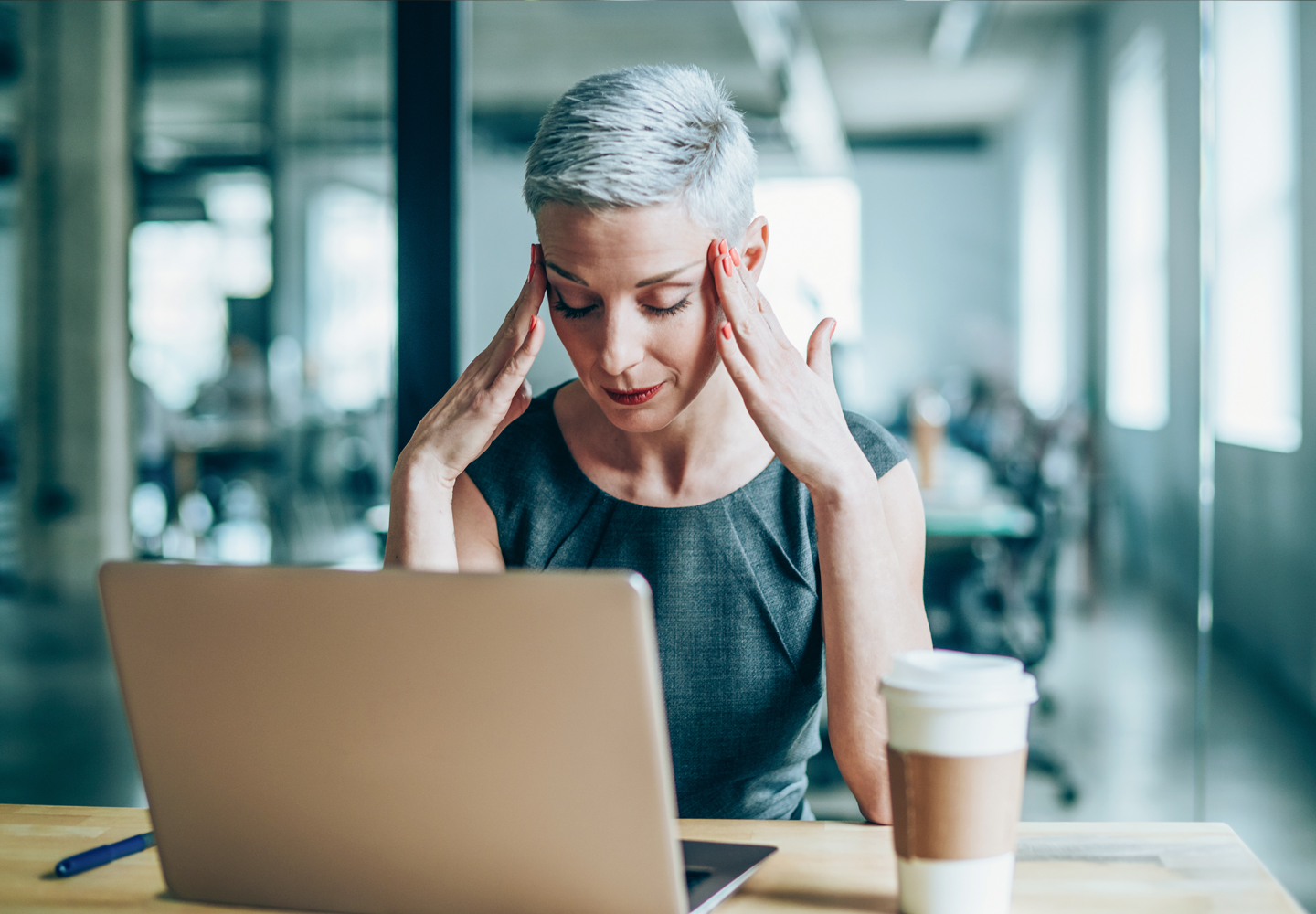 Stressed businesswoman with headache in the office