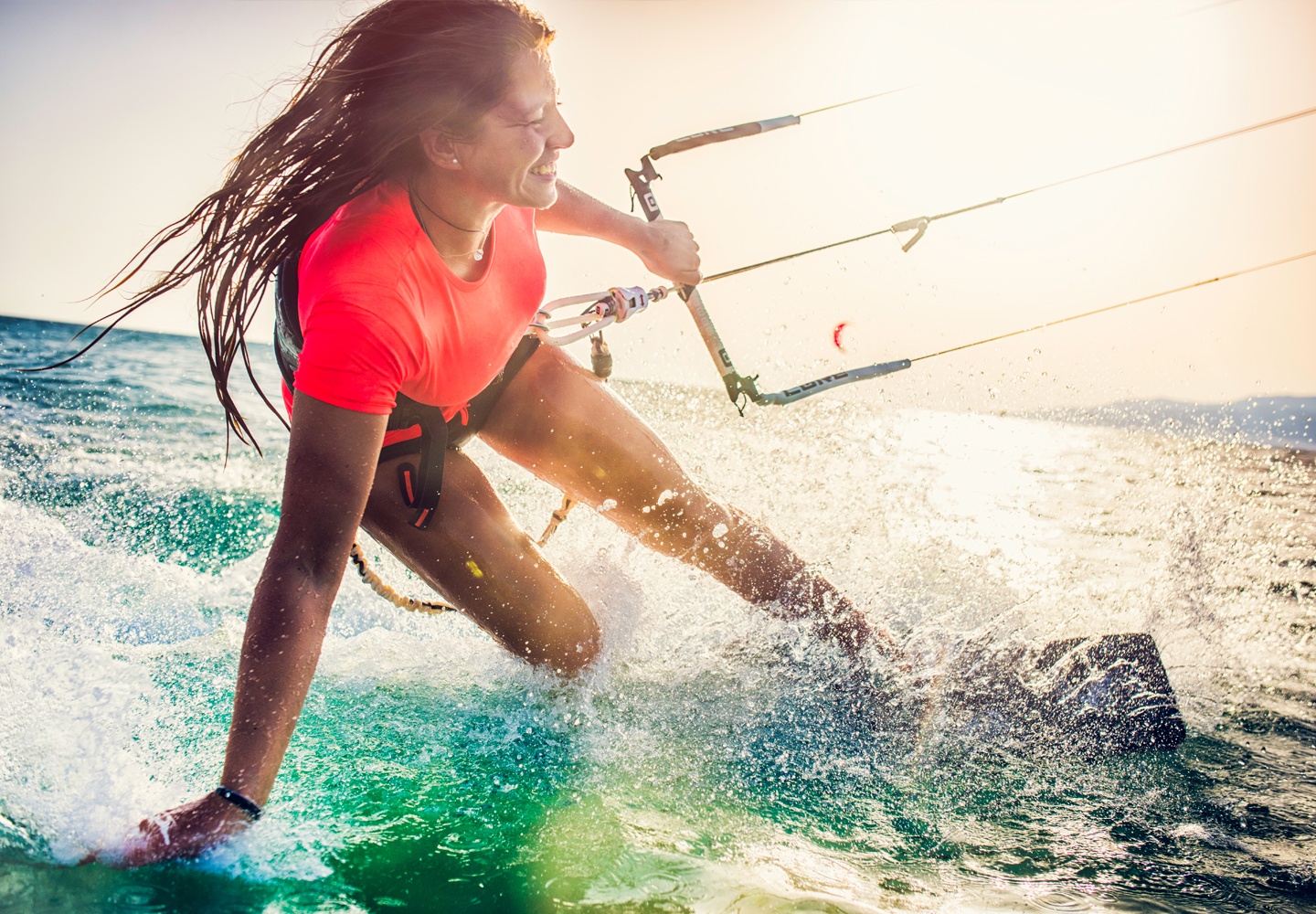 Smiling young woman kiteboarding on the sea