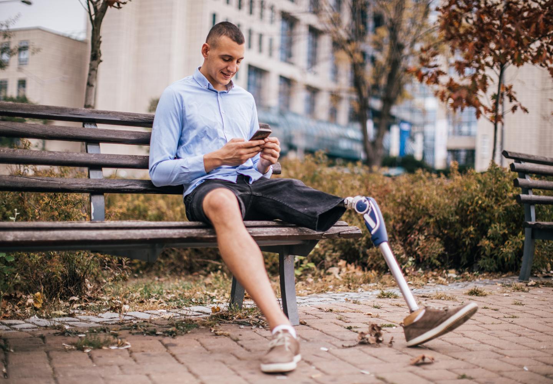 Man with prosthetic leg sitting on bench