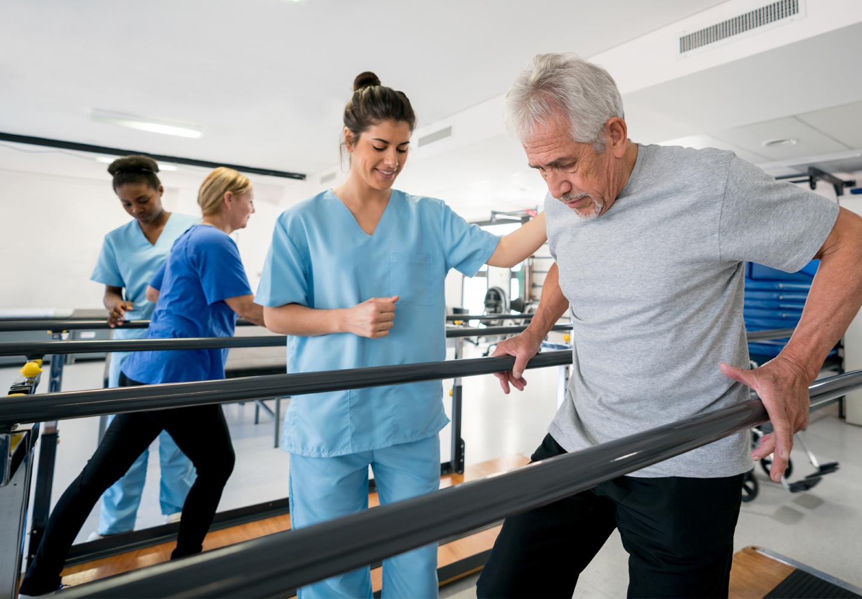 Team of physiotherapist helping senior patients walk between parallel bart